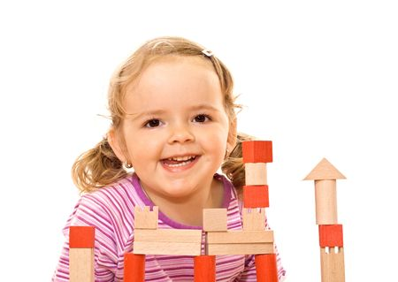 Happy girl posing behind a wooden blocks tower photo