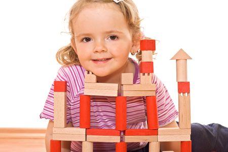 Cute girl posing behind a wooden blocks tower photo