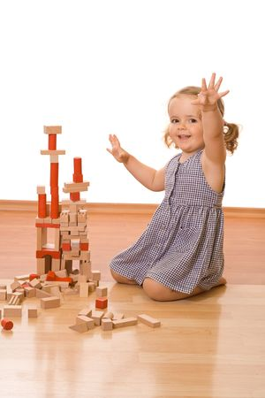 Happy little girl playing with wooden blocks on the floor - isolated Stock Photo