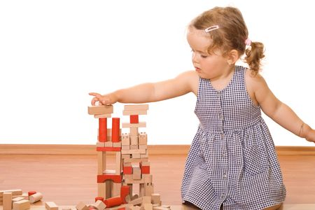 Cute little girl playing with wooden blocks photo