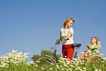 Woman and little girl riding a bike through a daisy field against blue sku Stock Photo
