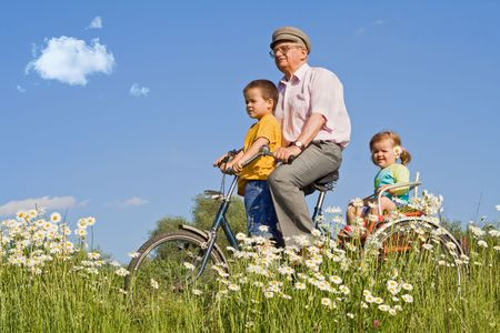 Kids riding with their grandfather on the daisies field againstr blue sky