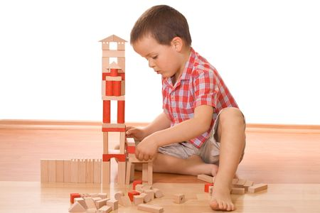 Little boy playing with wooden blocks - isolated photo