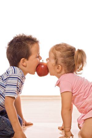 Little boy and girl bite into red apple - isolated feeding frenzy