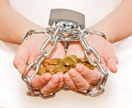 Saving money concept -  hands with golden coins, chained and locked