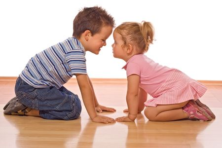 mischievous: Little boy doing some convincing or explaining on her little sister - isolated