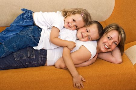Woman and kids playing togheter on the sofa photo