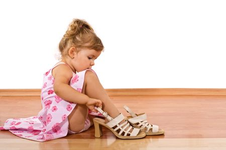 little girl sitting: Little girl trying her mothers shoes on the floor - isolated