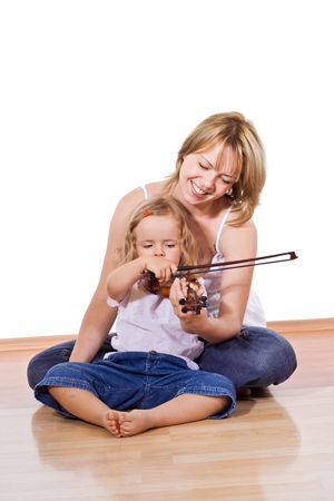 Woman sitting on the floor with a little girl playing and practicing the violin - isolated photo