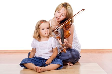 Woman and little girl enjoy playing and listening the violin together - isolated photo