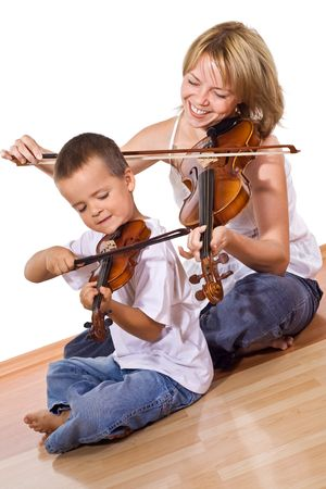 violins: Little boy with her mother playing or practicing the violin together sitting on the floor - isolated Stock Photo