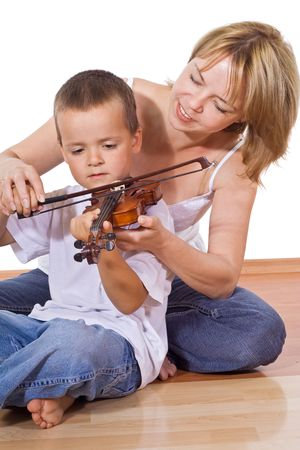 Woman teaching a little boy how to play the violin - isolated photo
