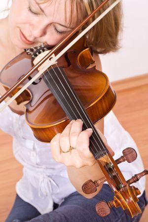 Mujer sentada tocando y disfrutando de dulces sonidos de un violín  Foto de archivo - 3309319