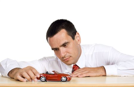 dream planning: Businessman playing with a red toy car, dreaming - isolated