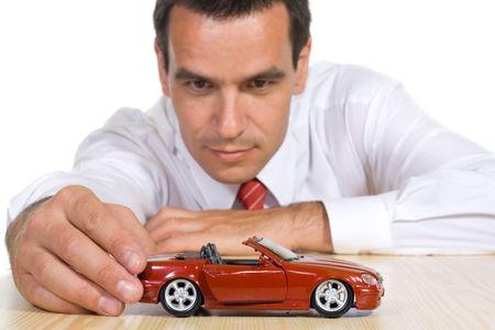 dream car: Empresario de juego con un auto de juguete de color rojo - aislados  Foto de archivo