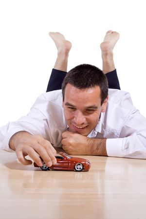 Businessman laying on the floor enjoying playing with a red toy car - isolated Stock Photo - 3333363