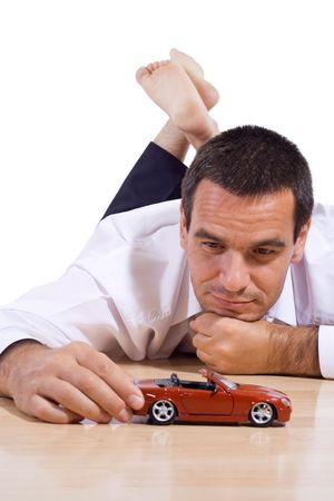 Businessman laying on the floor playing with a red toy car - isolated