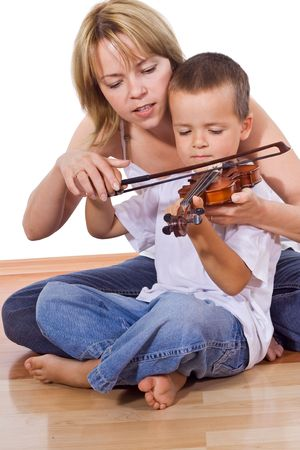 Little boy practicing the violin sitting on the floor with a woman - isolated photo