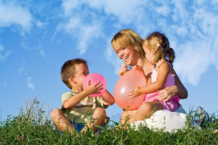 Woman playing with her kids and balloons in the grass outdoors against blue summer sky photo