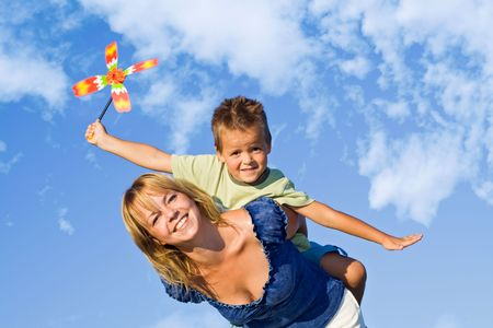 pinwheel: Woman and little boy playing with windmill toy against blue summer sky