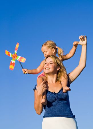 Woman and little girl playing outdoors with a propeller toy in the summer against blue sky Stock Photo - 3479435
