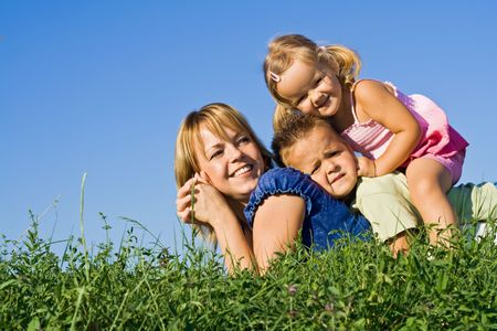 Smiling woman and kids in a heap laying on the grass outdoors photo