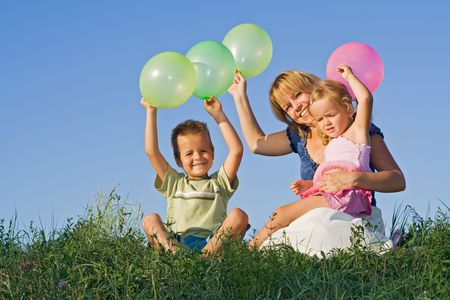 Kids and woman sitting on grass with balloons against blue summer sky photo