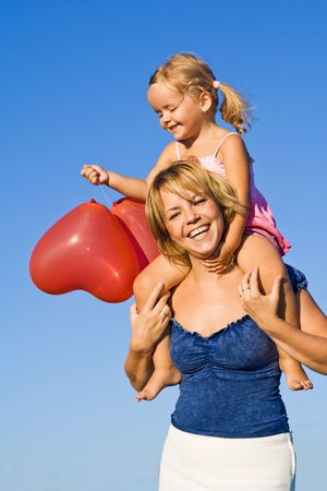 Woman and little girl having some balloon fun outdoors in summer time photo