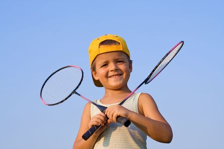 triumphant: Boy with two badminton rackets outdoors
