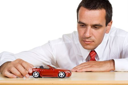 dream planning: Businessman playing with a red toy car contemplating the next business move - isolated Stock Photo