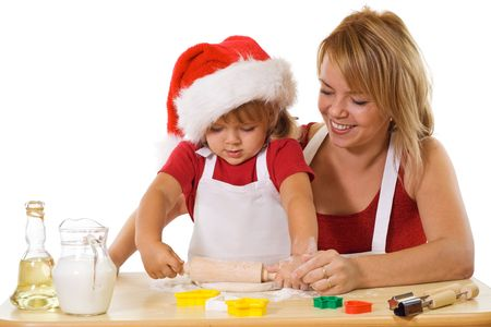 Woman and little girl stretching the christmas cookie dough - isolated photo