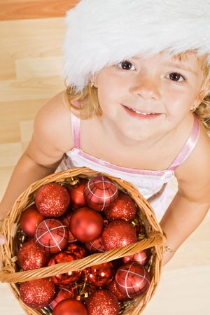 Little girl with a basket full of christmas balls and decorations photo