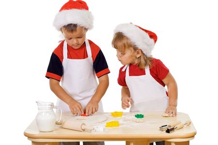 biscuit dough: Two kids preparing the christmas cookies - isolated Stock Photo