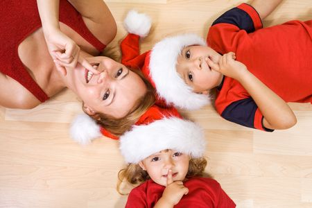 Woman and kids on the floor waiting for christmas and Santa Stock Photo
