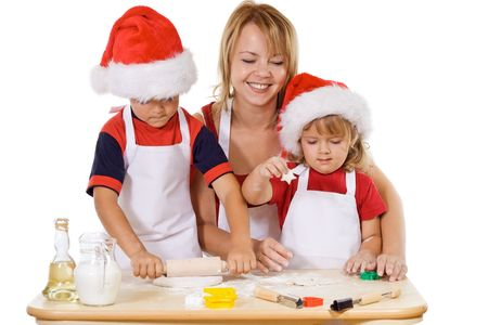 Woman and kids making christmas cookies wearing Santa hats - isolated photo