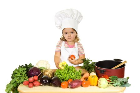 Little girl with a chefs hat, apron and lots of vegetables - isolated Stock Photo - 3688278