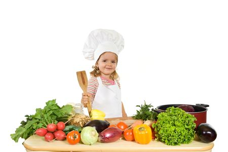 kids food: Happy little girl chef with lots of vegetables holding a wooden cooking utensil - isolated