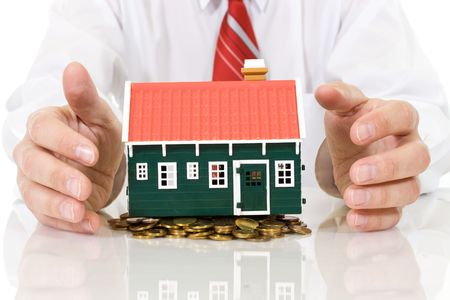 coins pile: House on golden coins pile with businessman hands protecting it - isolated, with reflection Stock Photo