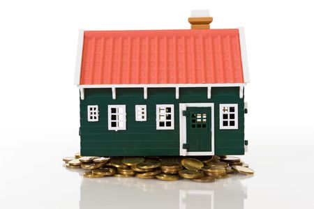 coins pile: Miniature house on golden coins pile - isolated with reflection Stock Photo