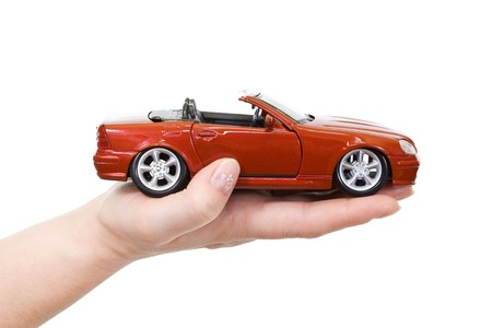 auto leasing: Woman hand with holding red sports car - isolated