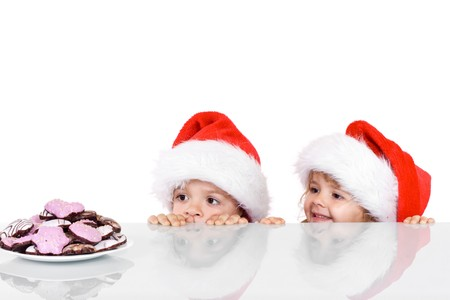 Two kids yearning for the christmas cookies - isolated