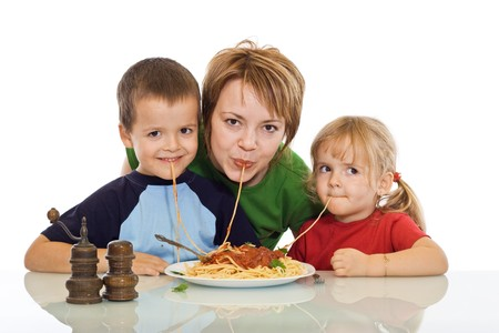 eating pasta: Happy smiling woman and kids eating pasta - isolated