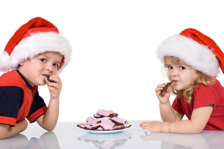 gingerbread cookies: Kids with santa hats eating gingerbread cookies at christmas time - isolated