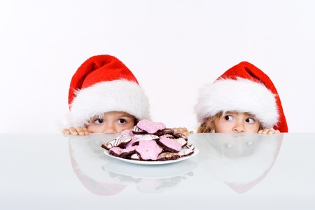Kids lurking to get a glimpse of santa, having gingerbread cookies as bait - on white background photo