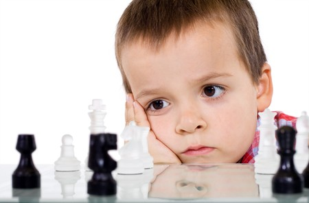 Boy playing chess - serious problem solving concept - isolated photo