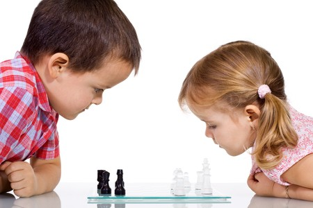 Serious kids playing chess - isolated photo