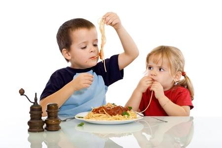 spaghetti saus: Twee kinderen eten pasta met hun handen - geïsoleerd