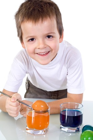 Happy boy smiling while dyeing the easter eggs - isolated photo