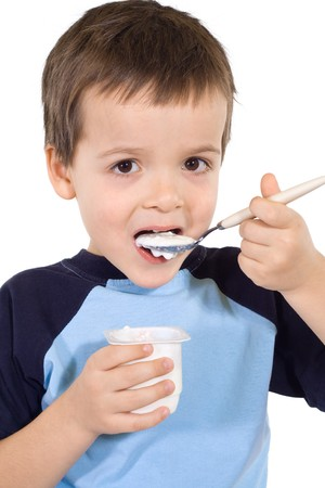 Little kid eating yoghurt with a large spoon - isolated photo