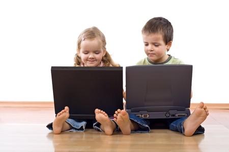 Niños sentados en el suelo utilizando computadoras portátiles - aisladas Foto de archivo - 4272453